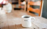 "Picture of white coffee cup with the words ""Begin"" on a table."