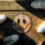 Smiley Face drawn on sidewalk with shoes in frame
