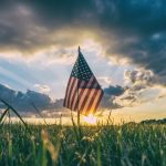 Picture of an American Flag amidst a blue sky and green grass